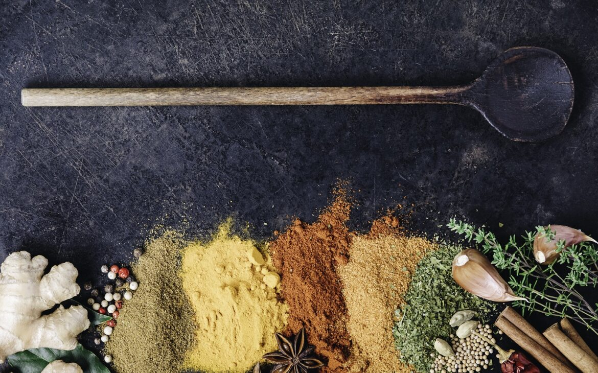 Spices, herbs, and a wooden spoon on a dark background